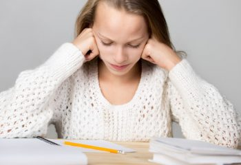 Portrait of stressed beautiful casual girl, sitting at desk, holding her head in arms with exhausted frustrated expression, cannot understand hard school task, studio, gray background