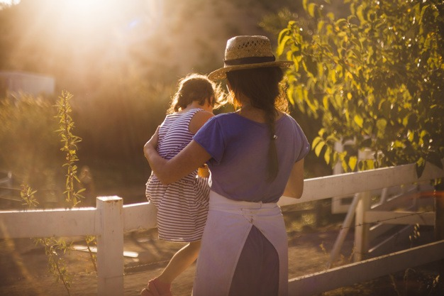 woman-with-her-daughter-near-white-fence-field_23-2147907123